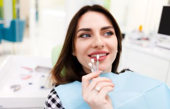 A young woman in a dental chair choosing color of veneers.